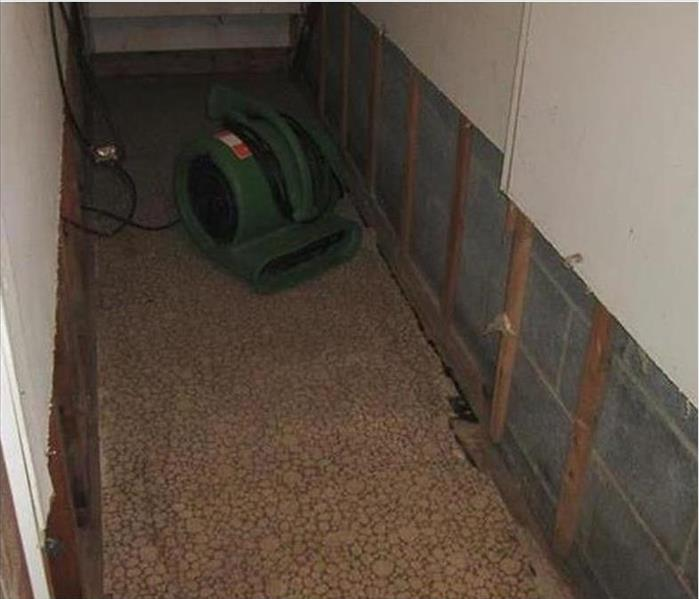 a flood cut to remove several feet of sheetrock and an air mover finishing the drying of the confined area