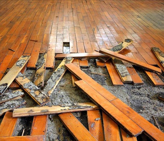 Badly damaged, moldy wood plank flooring is in the process of being removed