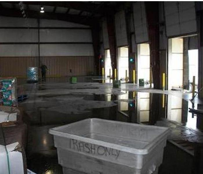 large puddles of water on a concrete floor in a warehouse, bay doors closeby