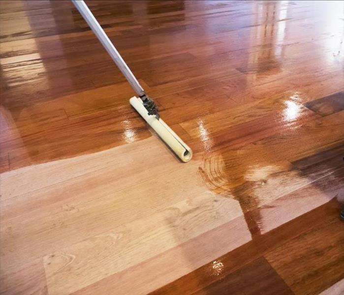 New, unfinished wood plank flooring is in the process of being refinished with stain and a polyurethane coating