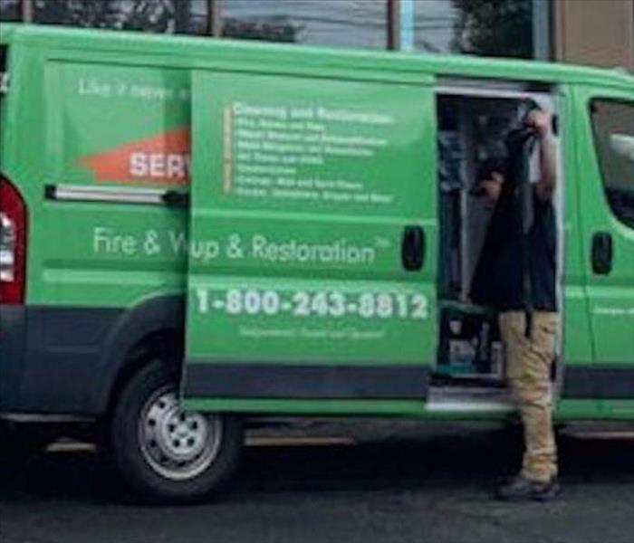 A SERVPRO employee in the back of a SERVPRO van.
