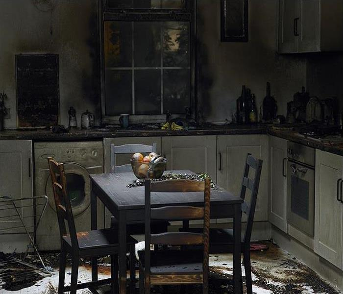 damaged kitchen after a fire and everything is covered in soot