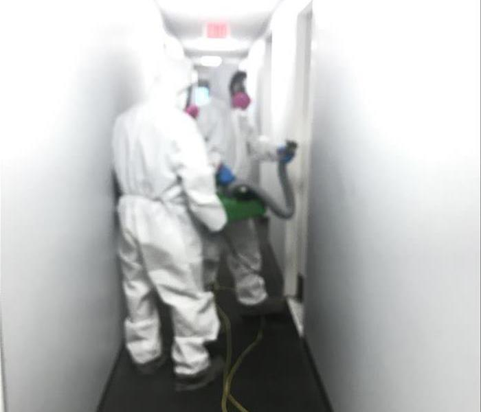 Two technicians spraying hallway with ULV