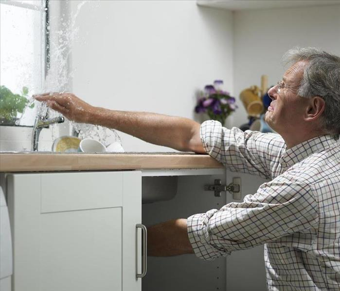 man tries to stop water squirting from the kitchen faucet